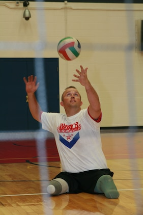 Marine veteran Bradley Walker throws up the ball for a serve during a scrimmage volleyball match with the U.S. Olympic Committee staff, the Colorado community, and a combination of Army, Navy, Air Force and Coast Guard athletes.  The event allowed the Marine athletes to practice and showcase their skills for the upcoming Warrior Games.  The Games will be held at the Olympic Training Center in Colorado Springs, Colo. May 16-21.