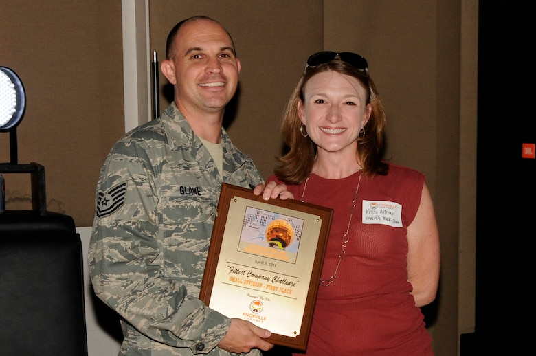 KNOXVILLE, Tenn. - Tech. Sgt. Jeffrey D. Glawe, left, an enlisted professional military education instructor at The I.G. Brown Air National Guard Training and Education Center at McGhee Tyson Air National Guard Base here, accepts a first place award for the Fittest Company Challenge from Kristy Altman, right, of the Knoxville Track Club during a ceremony in Market Square in downtown Knoxville, May 11, 2011.  (U.S. photograph by Master Sgt. Kurt Skoglund/Released)