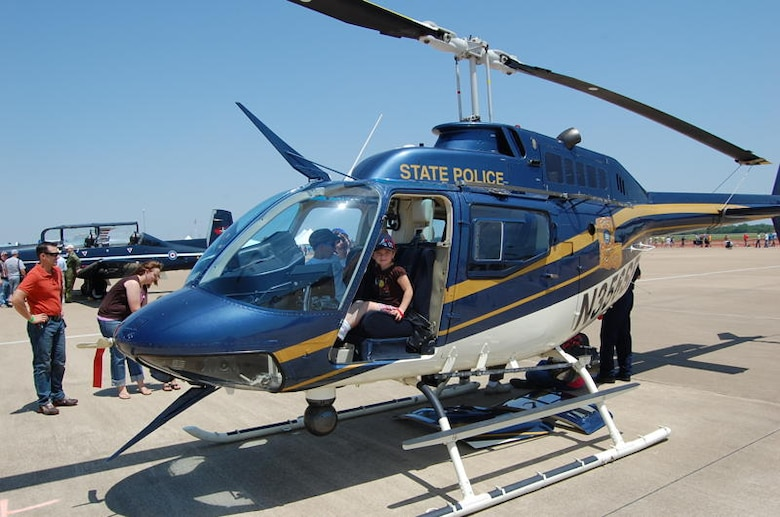 A young girl sits in the driver's seat of a Louisiana State Police OH-58 helicopter. The Louisiana State Police and local police and sheriff's offices all contributed various aircraft, vehicles and personnel to the air show as a show of the positive relationship Barksdale Air Force Base, La., enjoys with the surrounding communities. (courtesy photo by Staff Sgt. Matthew Connell, 26th Operational Weather Squadron)