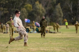 Cpl. Max King, mortarman, 3rd Battalion, 3rd Marine Regiment, 3rd Marine Division, III Marine Expeditionary Force, kicks an Australian rules football here May 14 during the 2011 Australian Army Skill at Arms Meeting (AASAM).  King was playing a game with Australian and Kiwi soldiers.  The week-long meeting pit military representatives from partner nations in competition through a series of grueling combat marksmanship events. Represented nations include Canada, France (French Forces New Caledonia), Indonesia, Timor Leste, Brunei, Netherlands, U.S., Papua New Guinea, New Zealand, Singapore, Malaysia, Thailand as well as a contingent of Japanese observers. (U.S. Marine Corps Photo by Lance Cpl. Mark W. Stroud/Released)
