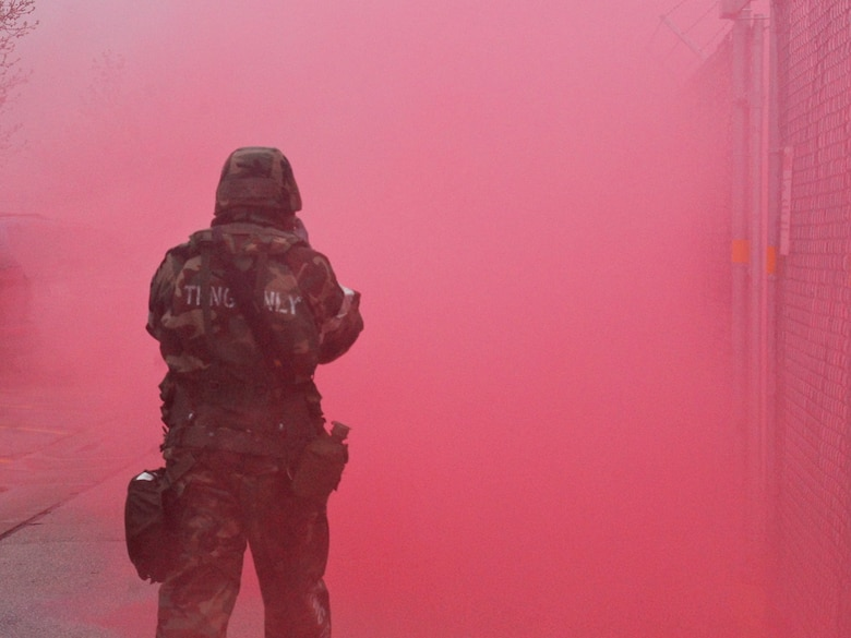 An Airman assigned to the 128th Air Refueling Wing, Milwaukee, navigates through the obscuring smoke of a simulated chemical attack during an Ability to Survive and Operate exercise at Gen. Mitchell International Airport on Saturday, May 14, 2011. The ATSO exercise tested the readiness and preparedness of Airmen to survive and operate during chemical, nuclear, and biological attacks.