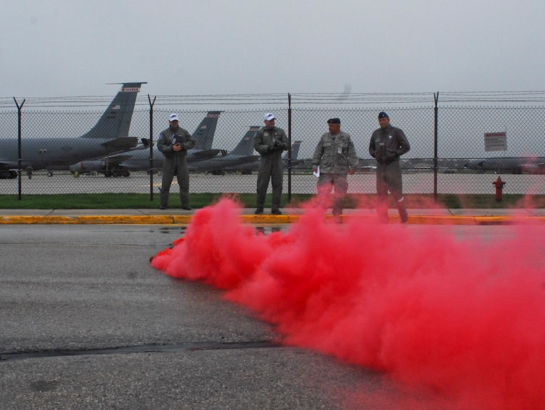 Monitoring officials from the 128th Air Refueling Wing, Milwaukee, activate a canister of colored smoke, which indicates a simulated attack upon the military installation, during an Ability to Survive and Operate exercise at Gen. Mitchell International Airport on Saturday, May 14, 2011. The ATSO exercise tested the readiness and preparedness of Airmen to survive and operate during chemical, nuclear, and biological attacks.