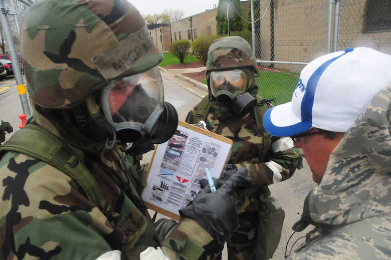 Airmen from the 128th Air Refueling Wing, Milwaukee, discuss their decisions and actions with monitoring officials during an Ability to Survive and Operate exercise at Gen. Mitchell International Airport on Saturday, May 14, 2011. The ATSO exercise tested the readiness and preparedness of Airmen to survive and operate during chemical, nuclear, and biological attacks. U.S. Air Force photo by Tech Sgt. Thomas J Sobczyk  / Released
