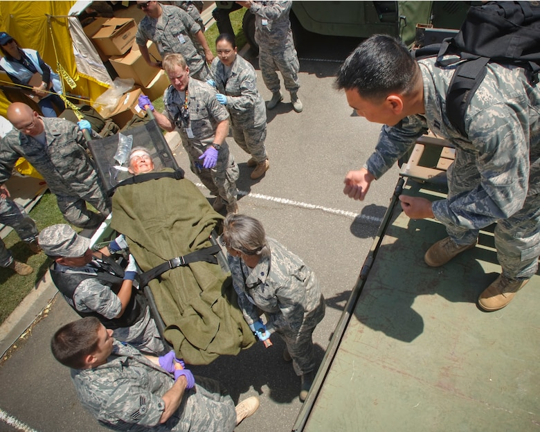 """U.S. Air Force Airmen Medical staff from the 163rd Reconnaissance Wing and the 146th Airlift Wing helps lift a victim volunteer into the bed of an U.S.. Air Force Humvee during """"Operation Medical Shelter,"""" a simulated disaster training exercise on May 11, 2011 at Freedom Park in Camarillo, California.. The exercise consisted of volunteers from local area hospital medical staff, law enforcement agencies, and local military state reserve. (U.S. Air Force photo by Airman 1st Class Nicholas Carzis/Not Released)"""
