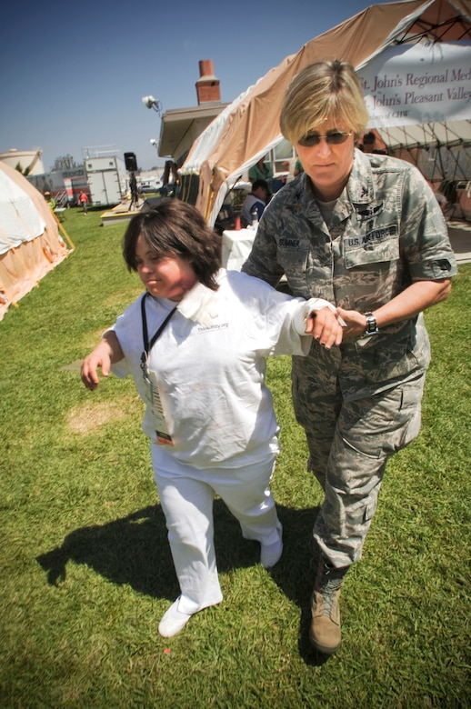 """U.S. Air Force Colonel Nancy Sumner, Commander of the 146th Medical Group, escorts a victim volunteer during """"Operation Medical Shelter,"""" a simulated disaster training exercise on May 11, 2011 at Freedom Park in Camarillo, California. The exercise consisted of volunteers from local area hospital medical staff, law enforcement agencies, and local military state reserve. (U.S. Air Force photo by Airman 1st Class Nicholas Carzis/Not Released)"""