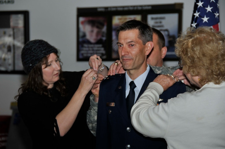Col. Steven J. Butow, 129th Rescue Wing Vice Commander, has his new rank pinned on by his wife Michelle (left), Brig. Gen. David S. Baldwin, The Adjutant General of the
