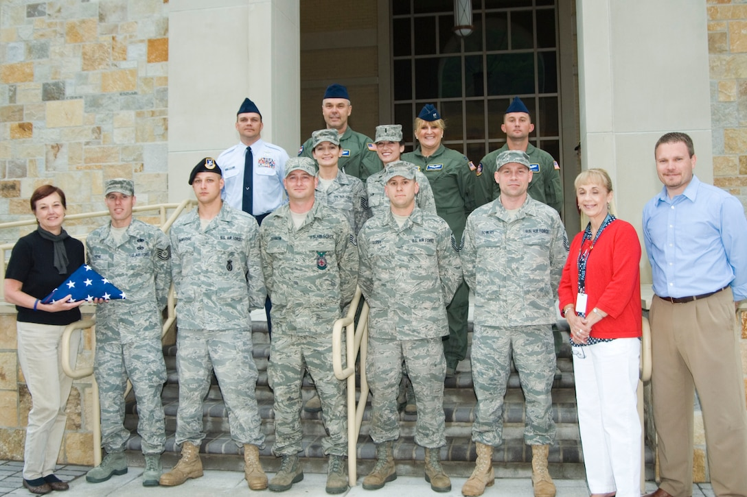 Airmen from the 167th Airlift Wing who call Morgan County home presented local officials with an American flag Saturday night to fly at the new courthouse in downtown Berkeley Springs, W.Va. Pictured in the first row, from left: Berkeley Springs Mayor Susan Webster, Tech Sgt. Sylvester Payne Jr., Staff Sgt. Luke Shambaugh, Staff Sgt. D.J. Zahnow, Master Sgt. Michael Darby, Master Sgt. Robert Bowers, Morgan County Commissioner Brenda Hutchinson and Morgan County Commissioner Brad Close. Second row, from left: Tech. Sgt. Gretchen Close and 1st Lt. Sarah Law. Third row, from left: Senior Master Sgt. Scott Wachter, Chief Master Sgt. Roland Shambaugh Jr., Capt. Carmela Emerson and Senior Airman John Unger rounding out the back row. (U.S. Air Force photo by Staff Sgt. Sherree Grebenstein)