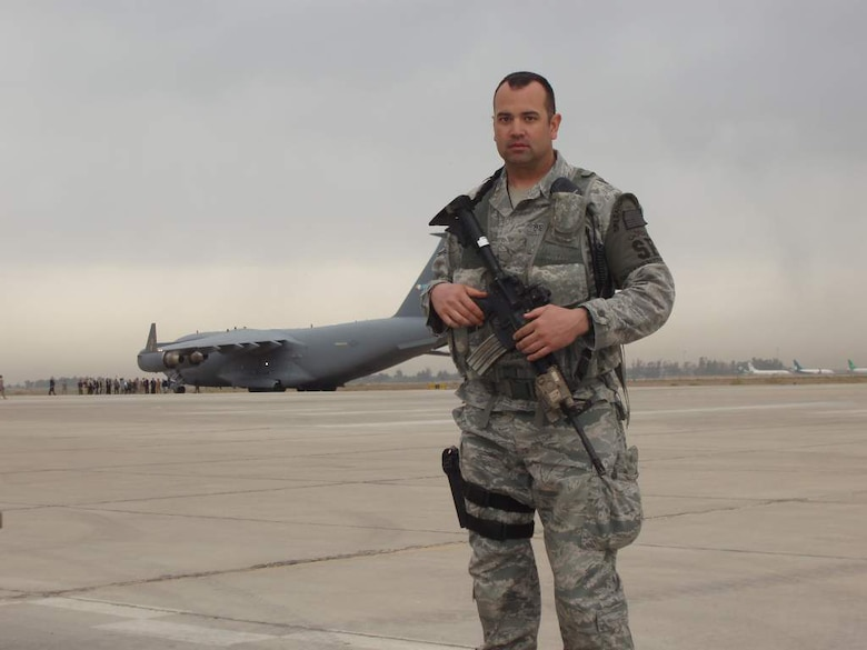 Staff Sgt. Ryan Demille, 151st Security Forces Squadron, Utah Air National Guard, poses in front of a C-17 on a flightline in Iraq. Sergeant Demille is on a six-month deployment to Iraq with the 151st SFS to assist airbase defensive forces in support of Operation New Dawn. U.S. courtesy photo (Released)
