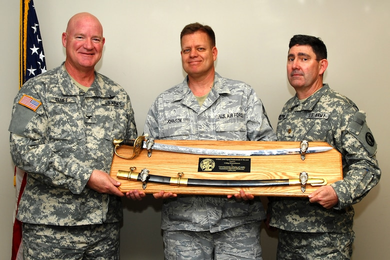 The Utah National Guard J6 Chief Information Officer, Col. Greggory Cluff, and Maj. Ben Morris, the state emergency communications manager, pose with the award winner, Chief Master Sgt. Don Johnson. Chief Johnson, a cyber systems branch chief with the 151st Communications Flight, was recently awarded the Utah National Guard?s 2010 Communications Professional of the Year. (U.S. Air Force courtesy photo)