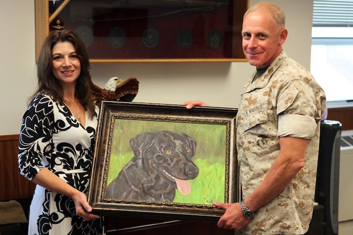 Caroline Carlson holds up a portrait with Maj. Gen. Melvin G. Spiese, the Deputy Commanding General for I Marine Expeditionary Force, during a presentation with Spiese. During the presentation Carlson explained what prompted her to paint the portrait of Sgt. Cole, a military working dog killed in Afghanistan.