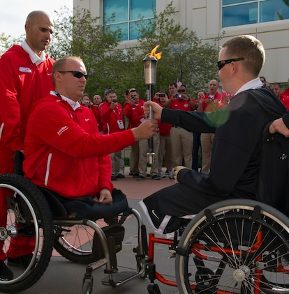 Army Pvt. 1st Class Joshua Bullis (right), Army team torchbearer, hands the 2011 Warrior Games torch to Marine veteran Cpl. Travis Greene (left), All-Marine team torchbearer, during the opening ceremony for the 2011 Warrior Games at the Olympic Training Center. The Warrior Games is an annual Paralympic-style competition for wounded, ill, and injured service members.