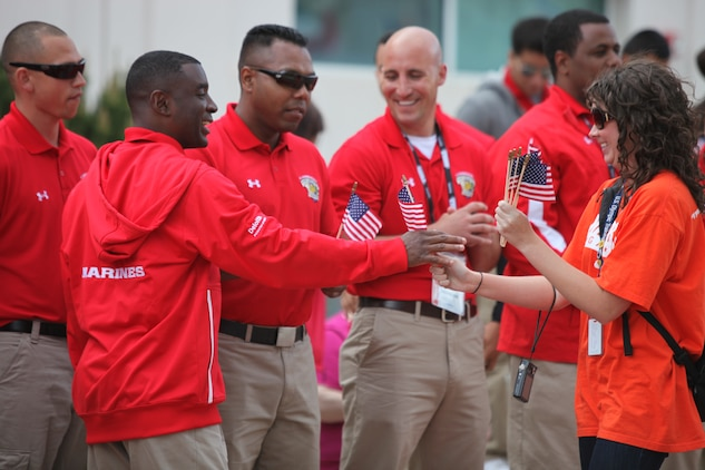 Civilian Volunteers hand out american flags to the All-Marine Warrior Games Team Coaches prior to the Opening Ceremony of the 2011 Warrior Games at the Olympic Training Center in Colorado Springs, Colo. May 16, 2011. U.S. Army, Marine Corps, Navy and Coast Guard, Airforce and Special Forces will compete  against one another over a period of five days.::r::::n::(U.S. Marine Corps photo by Lance Cpl. Kayla M. Hermann)
