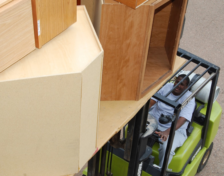 Staff Sgt. Trevor Hudson Lowers A Pallet Of Furniture From The Habitat For  Humanity ReStore