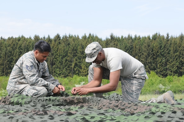 GEROLSTEIN, Germany – Staff Sgt. Alvin Delos Santos, left, 606th Air Control Squadron data systems technician, ties camouflage with Tech. Sgt. Modica Keenan, 606th ACS readiness NCO in charge, of as part of exercise Eifel Thunder 2011 in Gerolstein, Germany, May 9. The exercise tested the ability of Airmen to take all their equipment to an isolated location where they set up a deployed radar and satellite communications site as well as everything else required to survive and accomplish the mission in an isolated environment. (U.S. Air Force photo/Senior Airman Nick Wilson)