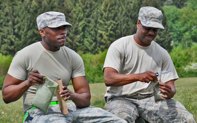 """GEROLSTEIN, Germany – Senior Master Sgt. Page Pinkney, left, 606th Air Control Squadron operations superintendent, eats a """"Meal, Ready to Eat"""" with Master Sgt. Khalifa Woodard, 606 ACS superintendent of operations training, during exercise Eifel Thunder 2011 in Gerolstein, Germany, May 9. The exercise tested the ability of Airmen to take all their equipment to an isolated location where they set up a deployed radar and satellite communications site as well as everything else required to survive and accomplish the mission in an isolated environment. (U.S. Air Force photo/Senior Airman Nick Wilson)"""