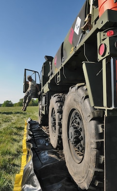 GEROLSTEIN, Germany – Staff Sgt. Dustin Smith, 606th Air Control Squadron power production journeyman, jumps out of a tactical vehicle after parking it on a plastic tarp to prevent oil from polluting the grass in case of an oil leak, as part of exercise Eifel Thunder 2011 in Gerolstein, Germany, May 9. The exercise tested the ability of Airmen to take all their equipment to an isolated location where they set up a deployed radar and satellite communications site as well as everything else required to survive and accomplish the mission in an isolated environment. (U.S. Air Force photo/Senior Airman Nick Wilson)