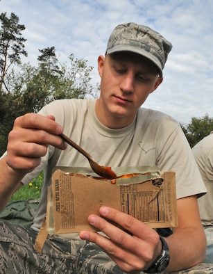 """GEROLSTEIN, Germany – Senior Airman Andrew Bastic, 606th Air Control Squadron power production apprentice, eats a chili and bean """"Meal, Ready to Eat"""" after arriving at the squadron's """"deployed"""" location as part of exercise Eifel Thunder 2011 in Gerolstein, Germany, May 9. The exercise tested the Airmen's ability  to take all their equipment to a deployed location and set up a deployed radar and satellite communications site as well as everything else required to survive and accomplish the mission. (U.S. Air Force photo/Senior Airman Nick Wilson)"""