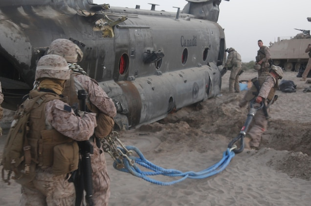 Helicopter support team Marines with 2nd Marine Logistics Group prepare the rigging for a transport of a Canadian Forces CH-47 Chinook helicopter during a tactical recovery of aircraft and personnel mission in Kandahar Province, Afghanistan, May 17. The Marines and Canadian Forces were able to transport the injured aircraft back home safely to Kandahar Airfield, Afghanistan.