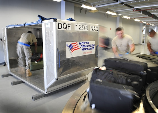 731 Air Mobility Squadron Airmen unload passangers baggage onto a moving belt belt, May 17 . (U.S. Air Force Photo by Senior Airman Evelyn Chavez)