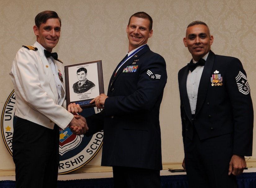 Capt. Ralph Ward and Chief Master Sgt. Jose LugoSantiago present the John L. Levitow Award to Senior Airman Michael Ault during the Airman Leadership School Class graduation May 12. The award is given for a student's exemplary demonstration of excellence, both as a leader and a scholar. Captain Ward is the Joint Base Charleston deputy commander and Chief LugoSantiago is the 628th Air Base Wing command chief. Airman Ault is an explosive ordnance disposal journeyman assigned to the 628th Civil Engineer Squadron. (U.S. Air Force photo/Senior Airman Katie Geiratz)