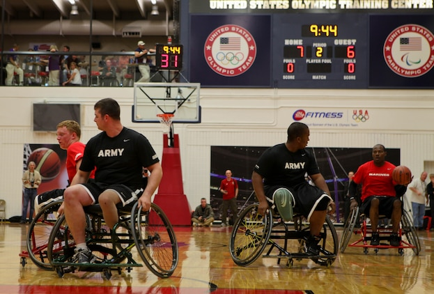 Sgt. Keith Buckmon (right) of the All-Marine wheelchair basketball team takes the ball down court while Lance Cpl. Joshua Wege works on getting open to set up an offensive play against the Army during the first game of wheelchair basketball May 17, 2011, at the Warrior Games in Colorado Springs, Colo. The Army beat the Marines 33-21 in the first game of the round robin series. Wheelchair basketball is a five-on-five game consisting of two 20-minute halves, and each team is required to have two players with lower limb impairments. The game is also a round robin event. All teams will compete against each other and seed based on their standings.