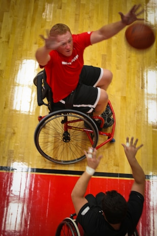 Lance Cpl. Joshua Wege of the All-Marine wheelchair basketball team plays tight defense against an All-Army member during the Marines vs. Army wheelchair basketball game May 17, 2011, at the Warrior Games in Colorado Springs, Colo. The Army went on to beat the Marines 33-21 in the first game of the round robin series. Wheelchair basketball is a five-on-five game consisting of two 20-minute halves, and each team is required to have two players with lower limb impairments. The game is also a round robin event. All teams will compete against each other and seed based on their standings.