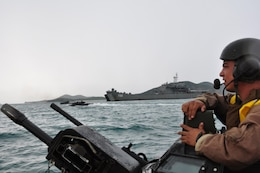 Sgt. Michael Uybungco, vehicle commander, 4th Assault Amphibian Battalion, 4th Marine Division, directs his amphibious assault vehicle past Royal Thai Navy medium landing ship HTMS Surin (LST 722) during an amphibious assault exercise May 18, as part of Cooperation Afloat Readiness and Training (CARAT) 2011.  This AAV was part of the second wave to hit the beach during a bilateral landing exercise with the Royal Thai Navy and Marine Corps.  The landing force, comprised primarily of reserve Marines from 2nd Battalion, 23rd Marine Regiment, was delivered to shore from the landing dock ship USS Tortuga (LSD 46) by Uybungco and fellow 'trackers' from his battalion. (U.S. Navy photo by Lt. K. Madison Carter)