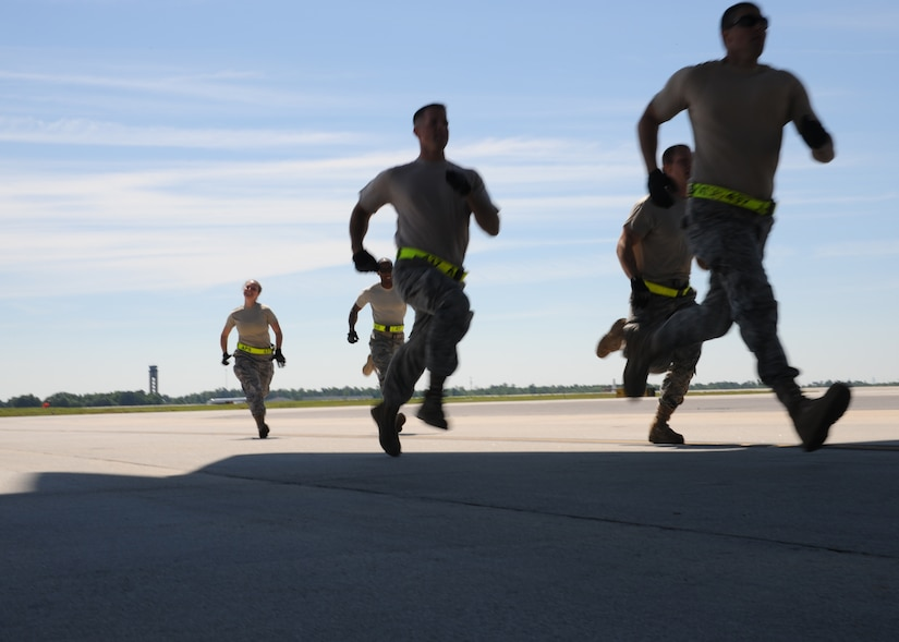The 437th Aerial Port Rodeo team runs to a Charleston C-17 on the Joint Base Charleston flightline, May 18. in preparation for the engine running onload/offload at the Rodeo competition where they will be tested against numerous other bases over career field knowledge, endurance, speed, teamwork as well as safety at Joint Base Lewis-McChord, Wash.(U.S. Air Force photo/Staff Sgt. Katie Gieratz)(RELEASED)
