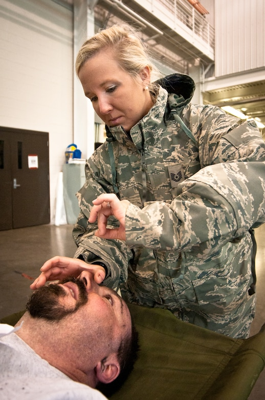Tech. Sgt. Heather Speidel, a medic with the Kentucky Air National Guard's 123rd Medical Group, simulates inserting a breathing tube in the windpipe of a notional plane-crash victim during earthquake-response exercises held May 18, 2011, at the Kentucky Air National Guard Base in Louisville, Ky. The exercises were designed to test the ability of the Department of Veterans Affairs and the Kentucky Air Guard to provide medical care following a major earthquake along the New Madrid fault line. (U.S. Air Force photo by Maj. Dale Greer)