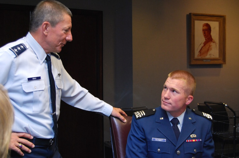 Lt. Gen. Mike Gould surrenders his seat to Cadet 1st Class Hal Schmidt during a meeting of the Air Force Academy Board at the Academy May 20, 2011. Cadet Schmidt, a native of Cody, Wyo., assigned to Cadet Squadron 22, was named the top graduate for the Academy Class of 2011 by the board based on his academic, military and physical fitness scores. General Gould is the Academy superintendent. (U.S. Air Force photo/Don Branum)
