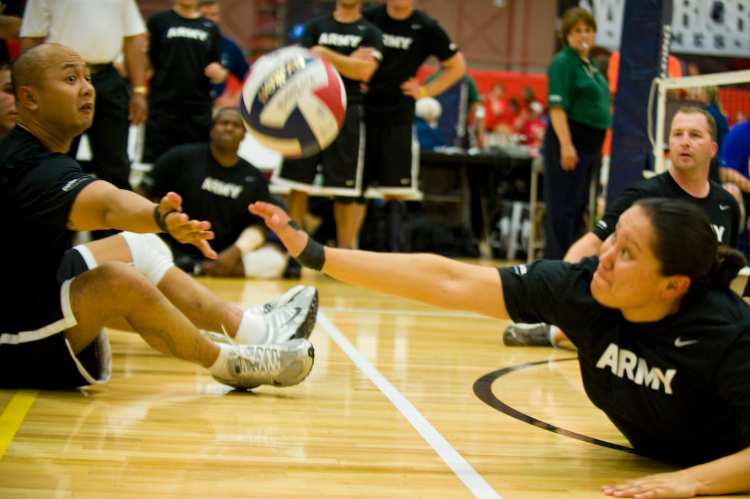 Members of the Army sitting volleyball team reach for the volleyball after being served by the Air Force May 19, 2011, during the the second annual Warrior Games in Colorado Springs, Colo. The Army won the series with two straight games. (U.S. Air Force photo/Staff Sgt. Christopher Griffin)