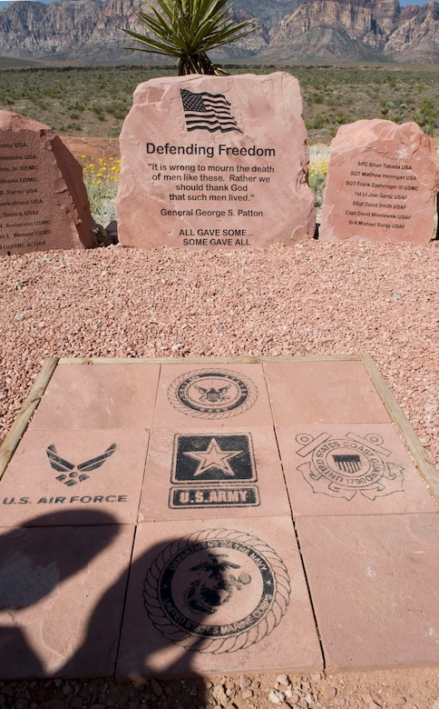 LAS VEGAS --The shadows of Nevada Congressman Joe Heck and his son, Joseph, are visible as they pay their respects at the Defending Freedom Memorial at Red Rock National Conservation Area May 14, 2011. Congressman Heck was a guest speaker at  the 6th annual Defending Freedom Memorial dedication ceremony. Hosted annually, the event honors fallen servicemembers with ties to Nevada and provides a forum for the community to express its appreciation for this sacrifice. The Defending Freedom Memorial was initially dedicated in 2005 and is comprised of seven sandstones with the engraved names of Nevada's fallen servicemen and women. This year, the names Nellis Airmen Senior Airman Michael Buras, Staff Sgt. David Smith, 1st Lt. Joel Gentz and Capt. David Wisniewski were added to the memorial. All four Airmen were lost in 2010 while supporting operations in Afghanistan.  (U.S. Air Force photo by Airman 1st Class Jamie L. Nicley)