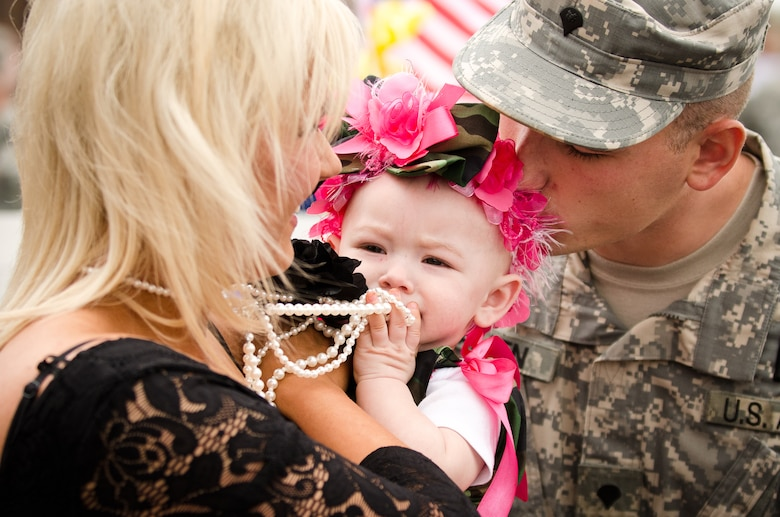 Spc. Justin H. Allen and his wife, Laura, hold their 9-month-old daughter, Elissa Skye, at the Kentucky Air National Guard Base in Louisville, Ky., during a welcome home ceremony May 1, 2011, for members of the Kentucky National Guard's Agribusiness Development Team II. Comprised of about 60 Army and Air National Guardsmen, KYADT II just returned from a 12-month deployment to Afghanistan, where they worked to make Afghani farmers become agriculturally self-sufficient, fostered business opportunities through a women's-empowerment initiative and provided force protection. Elissa Skye was born during Allen's deployment. (U.S. Air Force Photo by Maj. Dale Greer)