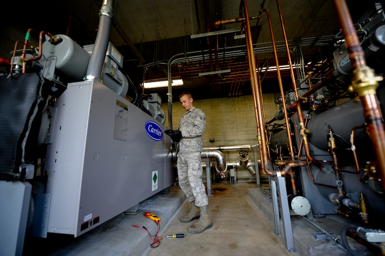 Senior Airman Derek Hunter, 18th Civil Engineer Squadron Heating, Ventilation, Air Conditioning and Refrigeration technician, thumbs through the remote control to a heating ventilation and cooling system April 21. In the past, Kadena's HVAC/R shop has had to replace large, outdoor, energy-wasting chiller units for buildings' AC systems on military installations across the island nearly every three years. Now,  Kadena recently instituted an initiative through the Air Force Smart Operations for the 21st Century program to replace the antiquated, over-oxidizing equipment with protected, indoor chillers to save the Air Force money. (U.S. Air Force photo/Staff Sgt. Jonathan Steffen)