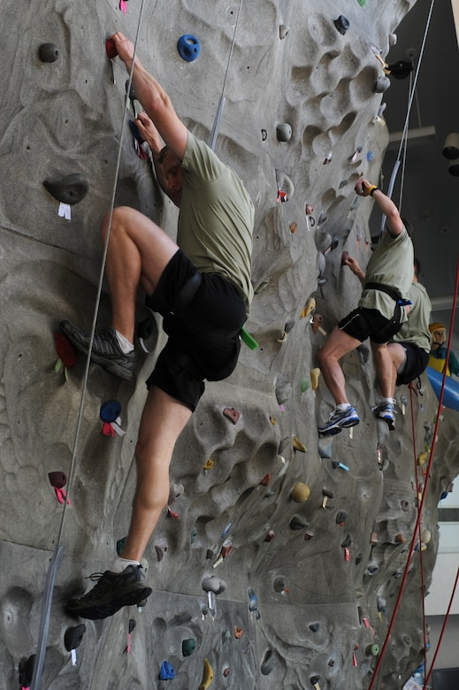 """Members of the Monster Mash team """"Hammer Time"""" climb the rock wall at the Outdoor Recreation Center on Joint Base Charleston - Air Base, May 19.  The Monster Mash event is 3.1 miles long and includes six challenging obstacles including a wall climb, truck push, mule pull, litter carry, jersey tug, and tire flip.  The Monster Mash was hosted by the 437th Operations Support Squadron.  (U.S. Air Force photo/ Staff Sgt. Nicole Mickle"""
