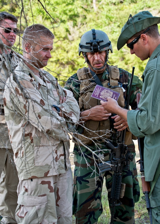 "Maj. Jeff Schmidt, team leader, discusses a passport found on a prisoner with ""simulated"" partner-nation special forces soldiers during the Combat Aviation Advisor course's Raven Claw exercise May 24 at Duke Field, Fla. As part of the exercise, 19 CAA students deployed to a foreign nation to advise and train their air forces in fixed wing and rotary aircraft operations.  The four-day exercise is the capstone of 12 weeks of baseline certification training for CAA.  The year-long process to become a CAA also includes months of language and flight training.  (U.S. Air Force photo/Tech. Sgt. Samuel King Jr.)"