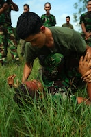 Lance Cpl. Andy Rivera, a rifleman from 2nd Platoon, Landing Force Company, grapples with an Indonesian Marine from 6th Battalion, 2nd Brigade, Korps Marinir, during martial arts training. Landing Force Company, comprised primarily of Marines from 2nd Battalion, 23rd Marine Regiment and 4th Assault Amphibian Battalion, 4th Marine Division, is participating in Cooperation Afloat Readiness and Training (CARAT) 2011. CARAT is an annual series of bilateral exercises held between the U.S. and Southeast Asian nations with the goals of enhancing regional cooperation, promoting mutual trust and understanding, and increasing operational readiness.  While in Indonesia, the service members from both nations will train together on martial arts, military operations on urban terrain, jungle warfare, combat marksmanship and combat lifesaving. (U.S. Marine Corps Photo by Cpl. Aaron Hostutler)