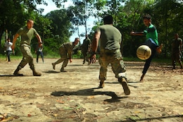 An Indonesian child kicks a ball into the  goal past Capt. Rudy Cazares, company commander with Landing Force Company. Marines with the company played a game of soccer with the children to build relationships with the surrounding community during a training pause. The Marines and Sailors, primarily from 2nd Battalion, 23rd Marine Regiment, are participating in Cooperation Afloat Readiness and Training (CARAT) 2011 through June. CARAT is an annual bilateral exercise held between the U.S. and Southeast Asian nations with the goals of enhancing regional cooperation, promoting mutual trust and understanding and increasing operational readiness throughout the participating nations.  While in Indonesia, the service members from both nations trained in martial arts, military operations in urban terrain, jungle survival, combat marksmanship, sniper techniques and combat lifesaving skills.