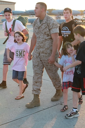 Marines of Marine Fighter Attack Squadron 122 reunites with spouses, children and siblings after stepping on to the flightline May 29. The Marines spent time while waiting for thier gear to be unloaded off of their aircraft.::r::::n::