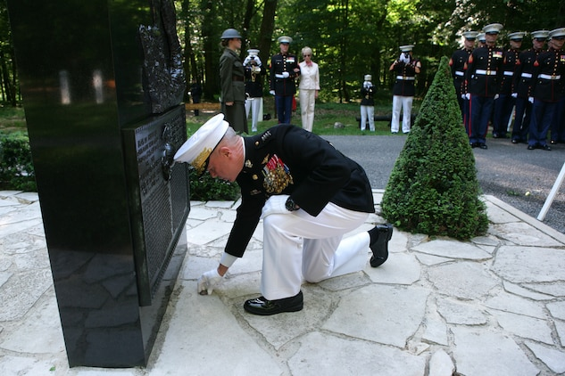 The 35th Commandant of the Marine Corps General James F. Amos lays a commemorative coin in front of the Iron Mike monument atop a hill in the heart of the Belleau Wood forest during a private Memorial Day ceremony in front of a formation of Marines and French soldiers. The coin is from the Marines of Task Force Belleau Wood, assigned to II Marine Expeditionary Force (Forward) in Regional Command (Southwest) in Afghanistan. The coin was given to the Commandant during his visit to Afghanistan, May 11-15, 2011.
