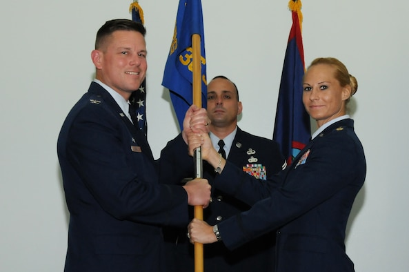 Col. Theodore Corallo, 36th Contingency Response Group commander (Left), passes the 736th Security Forces Squadron guidon to Maj. Tara Opielowski (right), newly appointed 736th SFS commander, during a change of command ceremony here May  26.(U.S. Air Force photo/ Senior Airman Carlin Leslie)