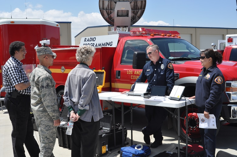 (from left) Barry Cannon, 452nd Communications Squadron; Airman 1st Class David Adolfo, 452nd Emergency Management Flight; and Nancy Driscoll, chief of bioenvironmental engineering and public health at March Air Reserve Base, exchange communication equipment ideas with Capt. Rich Atwood and fire dispatcher Barbara Selayndia of the Los Angeles County Fire Department .  The 3rd Annual Riverside County Multi-Agency Communication Interoperability Test was held at the Ben Clark Training Center in Riverside, Calif., May 19, 2011.  (U.S. Air Force photo/ Megan Just)