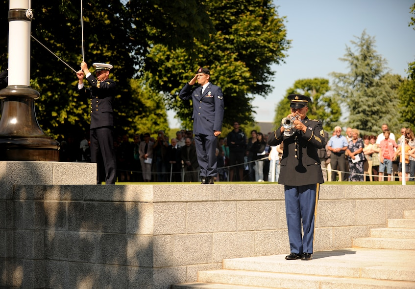 SAINT JAMES, France – U.S. Army Sgt. 1st Class David Martinez, U.S. Army Europe Band trumpeter, plays Taps as a French Sailor raises the U.S. flag during a memorial ceremony at Brittany American Cemetery and Memorial in Saint James, France, May 29. Brittany American Cemetery is the final resting place for 4,410 U.S. service members who died during the Normandy and Brittany campaigns of World War II in 1944. (U.S. Air Force photo/Senior Airman Nathanael Callon)