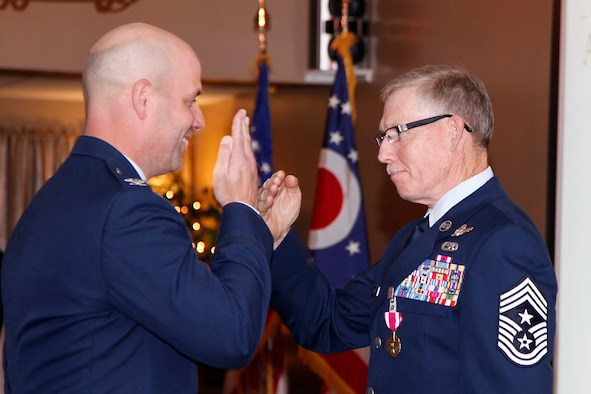 Command Chief Master Sgt. Greg Eyster salutes Col. Gary McCue after the presentation of a medal during the 179th Airlift Wing awards banquet Saturday, Oct. 22, 2011. The medal was presented to Eyster for meritorious service to the 179th AW over numerous years throughout his career. (U.S. Air Force photo by Master Sgt. Lisa Haun)