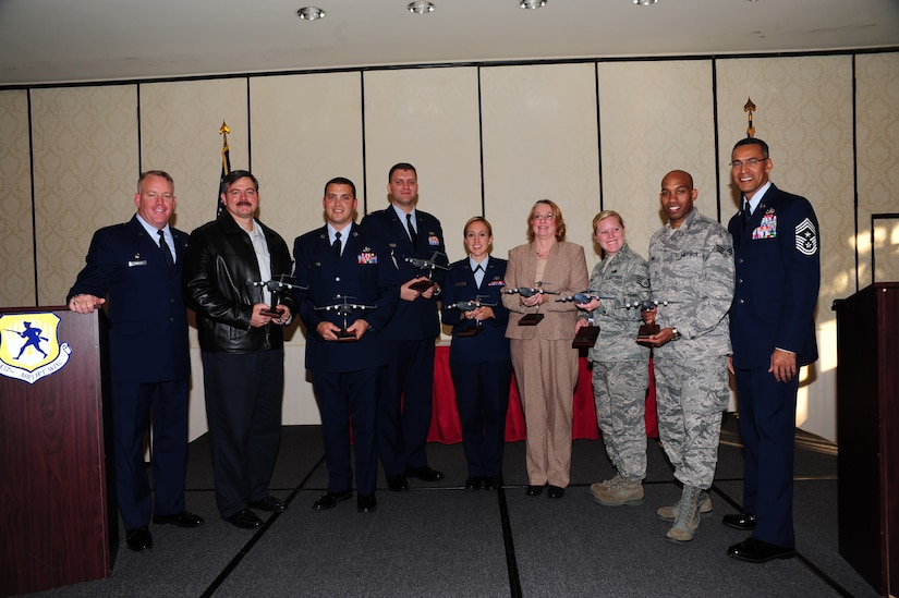 Col. Erik Hansen (left) and Chief Master Sgt. Terrence Greene recognize Mark Gardner, Master Sgt. Jamey Elms, Capt. Nicholas Lee, 2nd Lt. Whitney Hayes, Rhonda Perry, Staff Sgt. Courtney Rush and Senior Airman Marquis Jones as the 3rd Quarter Award winners during a ceremony at the Charleston Club Nov. 1. Hansen is the 437th Airlift Wing commander, Greene is the 437th AW command chief, Gardner is from the 437th Aircraft Maintenance Squadron, Elms is from the 437th Maintenance Squadron, Lee, Hayes and Perry are from the 437th Aerial Port Squadron, Rush is from the 437th AMXS and Jones is from the Operations Support Squadron. (U.S. Air Force photo/ Tech. Sgt Chrissy Best)