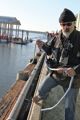 Todd Lawson, the recovery unit leader, pulls a rope guiding the deployment of a hard boom during spill management training at the Air Station fueling pier Nov. 2. Containment booms and hard booms are floats used during the exercise to help regulate the direction of spilled oil.