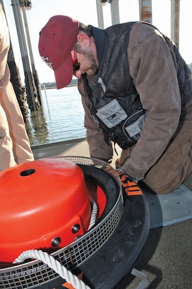 Jason Tomlinson, a spill management team member, attaches a vacuum hose to a skimmer during spill management training at the Air Station fuel pier Nov. 2. A skimmer is used to extract oil from water using a vacuum and back truck, a truck holding a large empty tank.