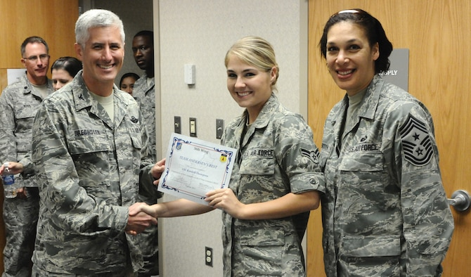 ANDERSEN AIR FORCE BASE, Guam—Airman 1st Class Kendall Thompson, 36th Medical Group emergency medical services technician, receives the Team Andersen's Best award from Col. Donald Drechsler, 36th Wing vice commander, here Oct. 27. Each week, supervisors nominate a member of their team for outstanding performance and the wing commander presents the selected Airman/Civilian with an award. (U.S. Air Force photo by Senior Airman Benjamin Wiseman/Released)