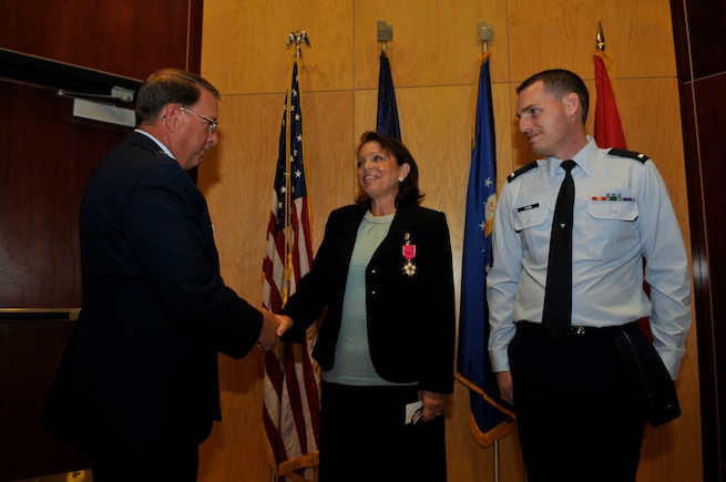 Brig. Gen. Wayne E. Lee presents the Legion of Merit award in honor of the late Col. Bruce C. Evans to his wife, Mrs. Connie Evans, and his son, 1st Lt. Benjamin Evans.  Colonel Evans was awarded the Legion of Merit posthumously for exceptionally meritorious conduct as the state staff Judge Advocate with the Utah Air National Guard Headquarters. (Air Force photo by TSgt Jeremy Giacoletto-Stegall)
