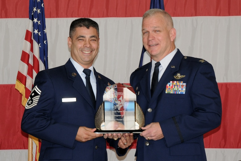 Col. Drew DeHaes (right) presents Senior Master Sgt. Hector Arias (left) with the First Sergeant of the Year award during the 2011 Awards Ceremony held in the hangar of the 132nd Fighter Wing, Des Moines, Iowa on November 6, 2011.  (US Air Force photo/Staff Sgt. Linda E. Kephart)(Released)